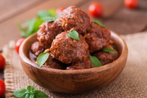 meatballs sweet sour tomato sauce basil wooden bowl